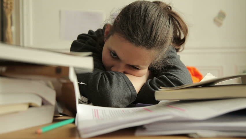 Female student looking tired of studies. Around her are piles of books and papers #4032541