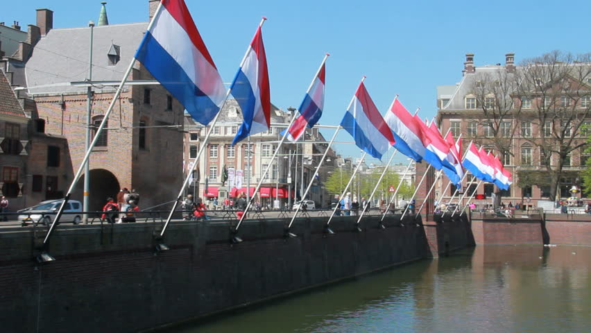 THE HAGUE, HOLLAND, MAY 5: Tram drives past large Dutch flags at the Dutch political center Binnenhof on May 5, 2013 in The Hague, Holland. The Hague is the residence of the Dutch parliament.