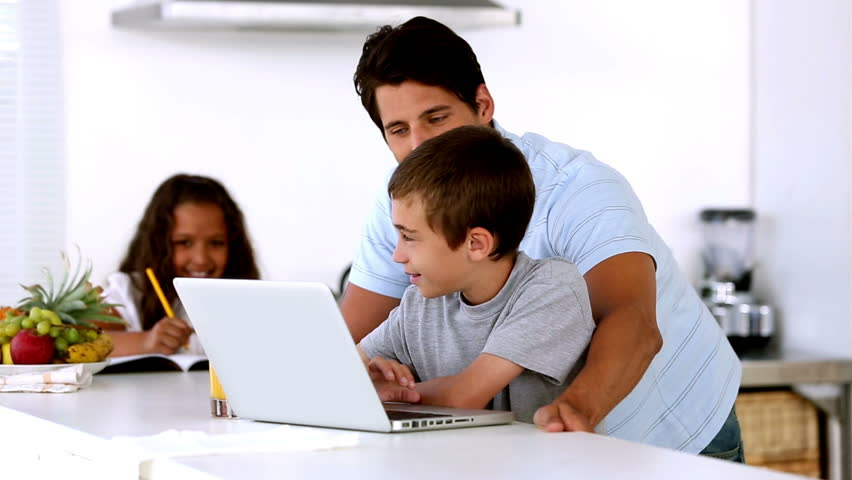 Father looking at laptop with son and mother enters to help daughter in the kitchen | Shutterstock HD Video #4047823