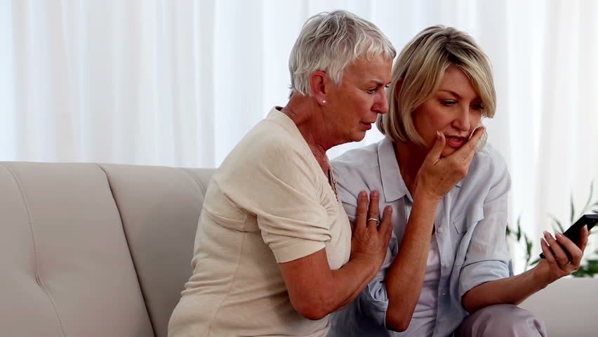 Mother and daughter on the couch reading a bad news on a text message | Shutterstock HD Video #4049356