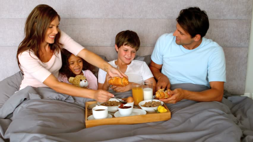 Family having breakfast in bed together in the bedroom in slow motion at 250 frames per second Social distancing and self isolation in quarantine lockdown for Coronavirus Covid19