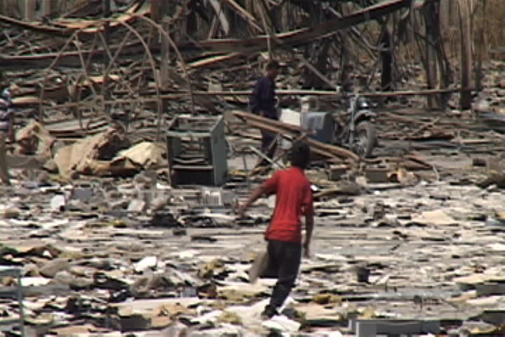 BAGHDAD, IRAQ - JULY 26, 2003: Boy runs through rubble and debris, then slows to a walk.