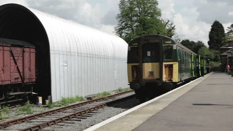 British Railway: A pan and track shot across the front of an old-style British Rail diesel train standing in a traditional English rural train station.