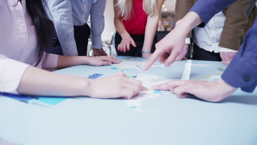 A business team of mixed ethnicity are working in a light and modern open plan office. They are looking at a map of the world and discussing possibilities for future business ventures. In slow motion. | Shutterstock HD Video #4130941