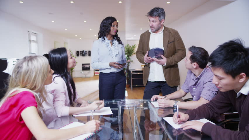 An attractive and enthusiastic mixed ethnicity team of young architects are holding a business meeting and brainstorming. They are discussing solar panels and development of scientific silicone. | Shutterstock HD Video #4130974