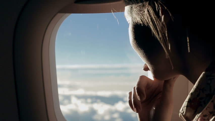 Girl looks at the clouds from airplane window | Shutterstock HD Video #4143106