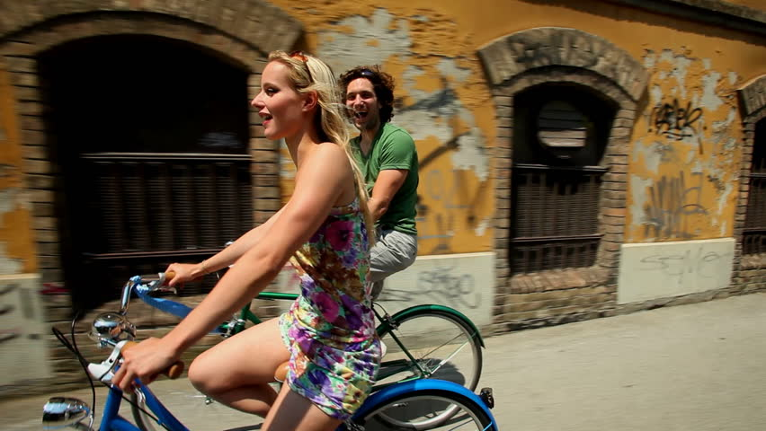 Couple cycling in town on sidewalk lane past old abandoned building