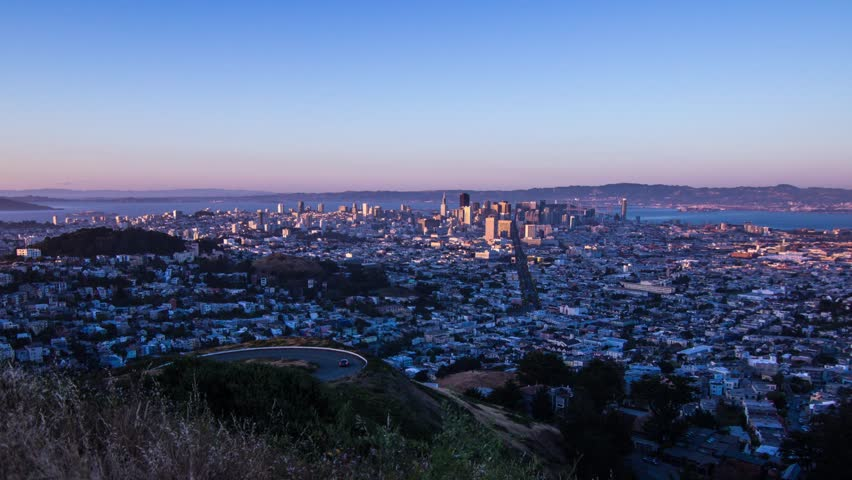 Day to Night Time Lapse of Downtown San Francisco from Twin Peak. View of Market Street and Bay Bridge overlooking the traffic from sunset time to dark night sky.