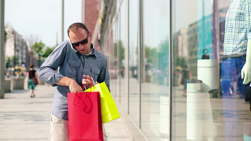Man with shopping bags talking on cellphone in the city