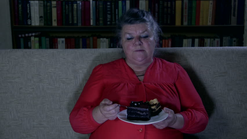 Fat senior woman watching tv show and eating cake at night