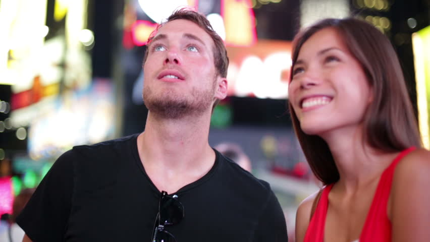 Happy young couple on Times Square, Manhattan, New York City at night. Beautiful young multi-ethnic couple dating smiling having fun on date or as tourists in USA. Asian woman, Caucasian man. | Shutterstock HD Video #4195030
