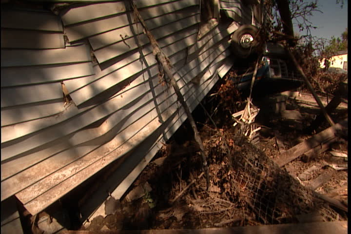 Side of crumpled house atop overturned truck, camera pans right across yard filled with debris in New Orleans after Hurricane Katrina (October 2005).
