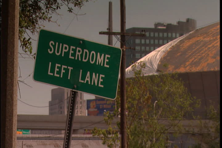 Street sign for Superdome and damaged roof of Superdome in background in New Orleans after Hurricane Katrina (October 2005).