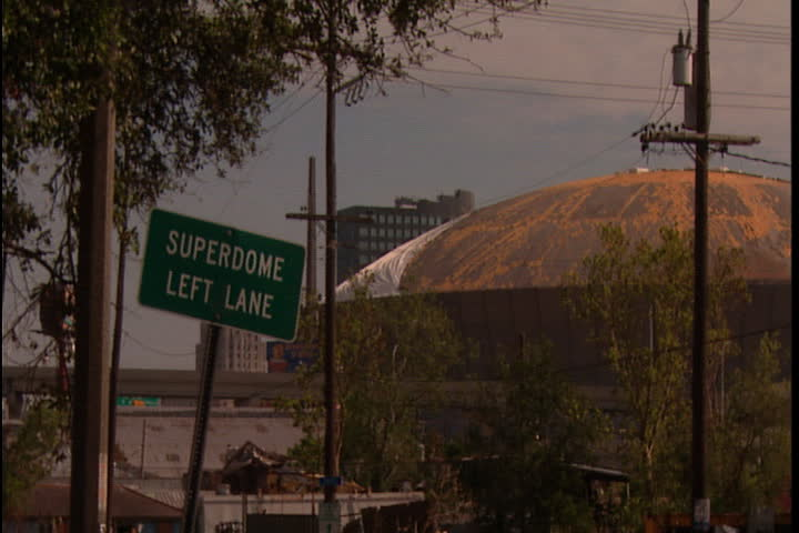 Street sign for Superdome, camera zooms in to damaged roof of Superdome in New Orleans after Hurricane Katrina (October 2005).