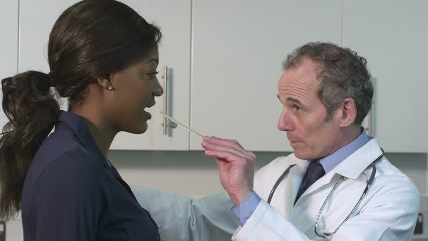 Older male doctor examining young black patient