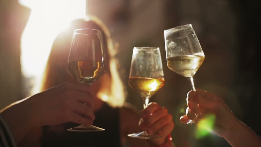 Women holding glasses of white wine making a toast at sunset #4227259