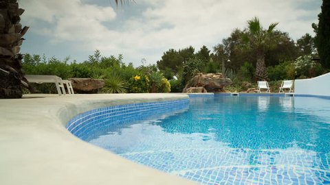 a luxury private swimming pool surrounded by a paradise garden