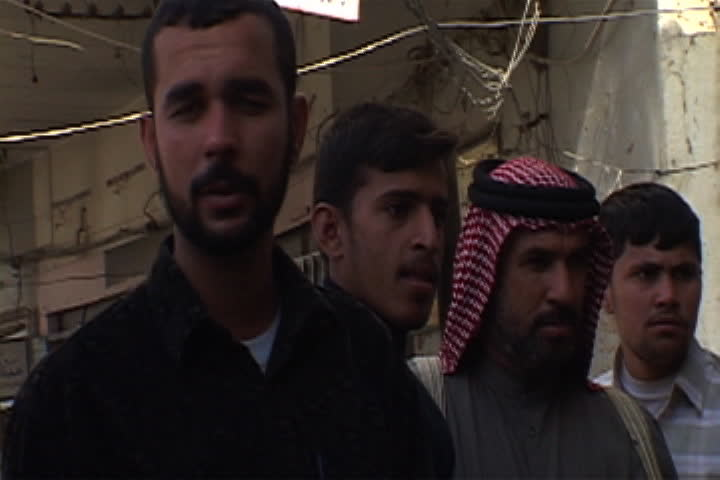 NASIRIYAH, IRAQ - DECEMBER 14, 2003: Faces of a small group of Iraqi men, one is wearing a red and white keffiyeh.