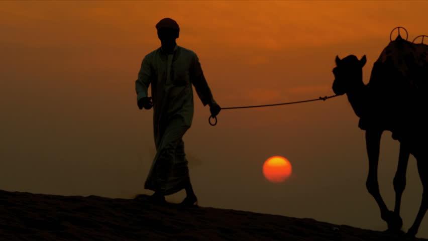 Arab male traditional headdress robe walking his camels over desert sand dunes silhouette sunset shot on RED EPIC | Shutterstock HD Video #4246481