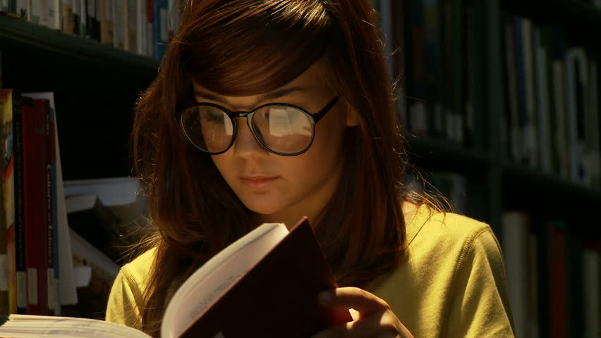 Close up on female high school student reading a book in a library. | Shutterstock HD Video #4253042