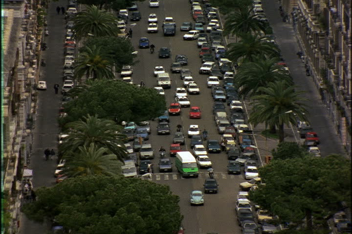High angle view of traffic on Naples street, zoom out to show apartment buildings, coastline and Mount Vesuvius in Naples, Italy | Shutterstock HD Video #4277852