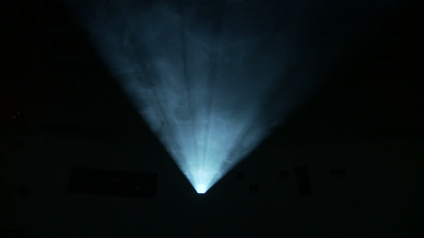 Low, front on view of the light beam of a 35mm projector running in a darkened movie theater.  Frame rate is different from projector speed, enhancing flickering effect. #4283507