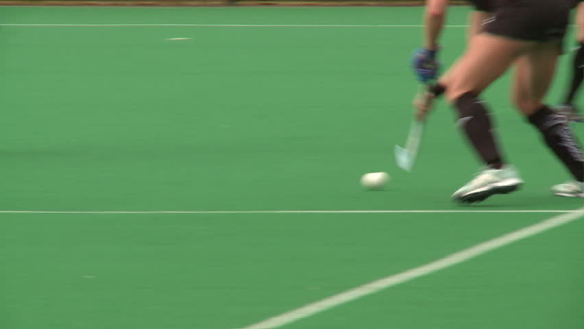 Field Hockey played on astro turf. woman's field hockey played on a rainy day in London. #4320347