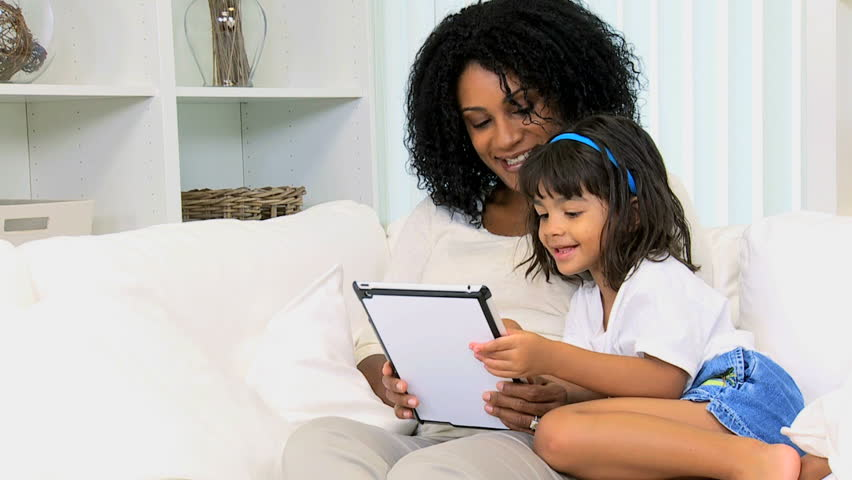 Cute little ethnic girl home with young mother using wireless tablet #4330790