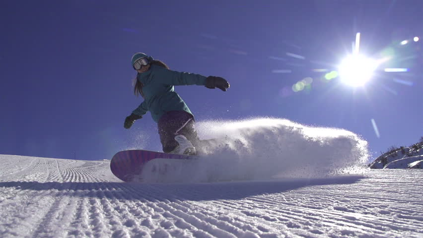 SLOW MOTION: Snowboard girl spraying snow into camera