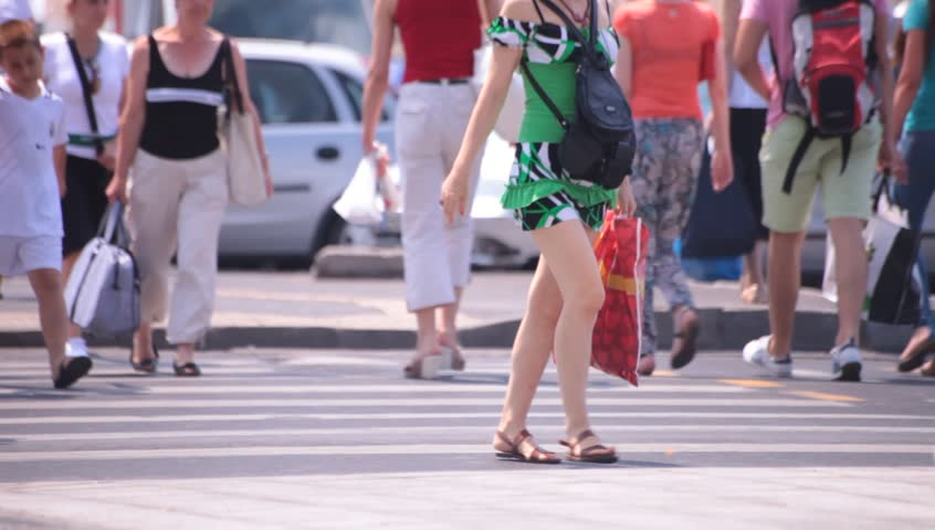 Hot sexy legs of young adult women walking down the street. Hot summer weather.