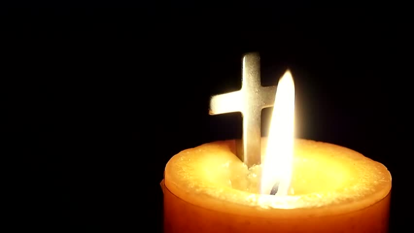 Candle burning with a christian cross. Great to use in your religious projects.