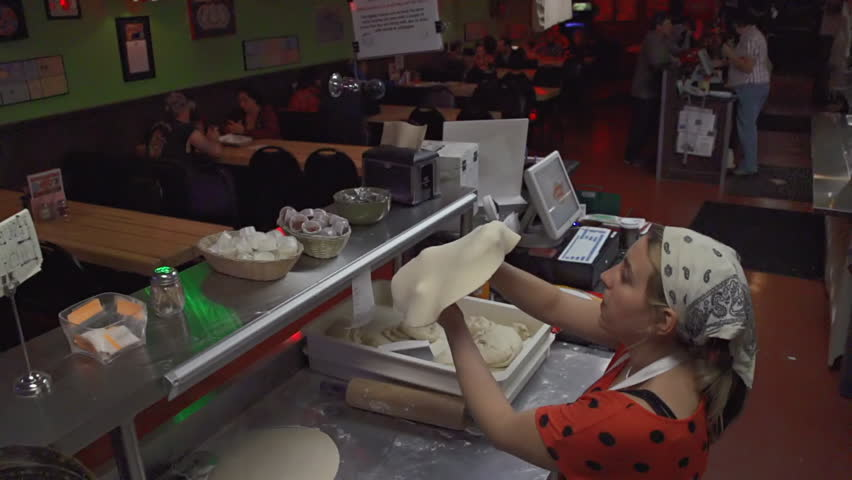 A young woman tosses pizza dough in slow motion in a pizzeria
