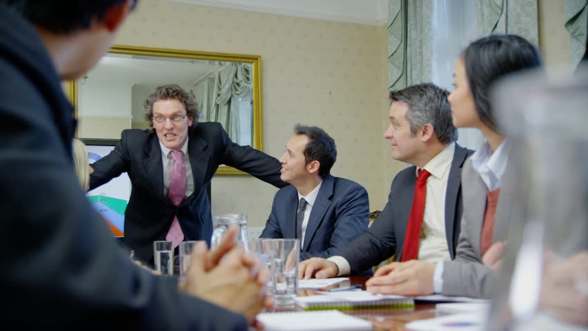 Happy and enthusiastic business team of mixed ages and ethnicity are seated around a conference table for a business meeting. They reach across the table to shakes hands with one another. Slow motion. Royalty-Free Stock Footage #4375133