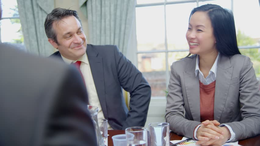 Happy and enthusiastic business team of mixed ages and ethnicity are seated around a conference table for a business meeting. They reach across the table to shakes hands with one another. Slow motion. #4375211