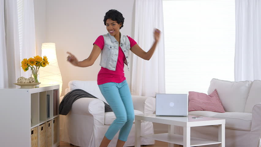 African American woman in jean vest dancing in living room
