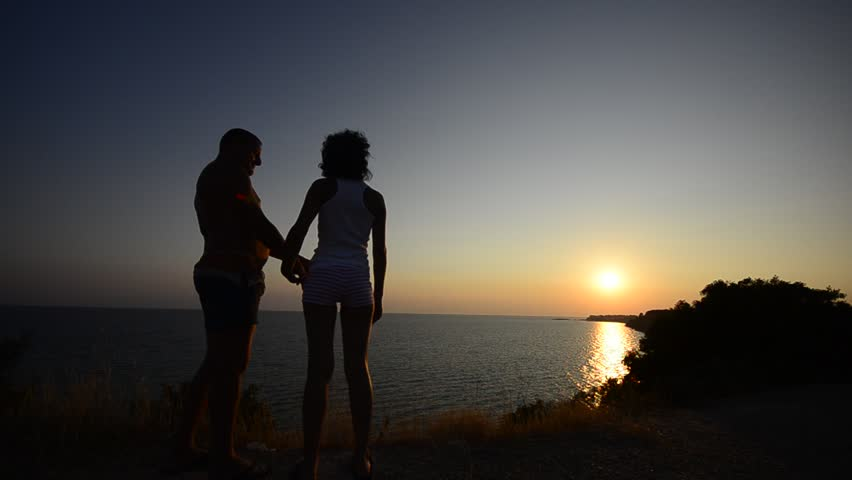 Romantic couple hug and kiss on the ocean beach sunset, Romance on the beach silhouetted by the sparkling water