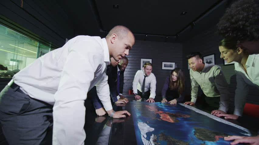 Young  modern business team of mixed ethnicity, holding a brainstorming meeting around a conference table with a map of the world. In slow motion. | Shutterstock HD Video #4388099