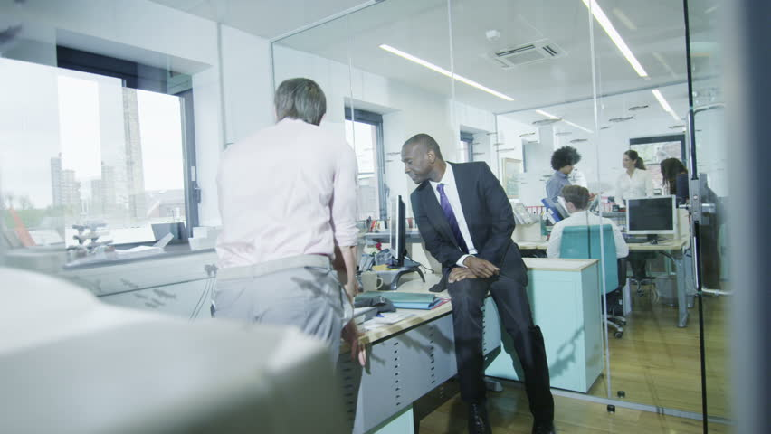Attractive mixed ethnicity business group working together in an informal modern office. In slow motion. | Shutterstock HD Video #4389608
