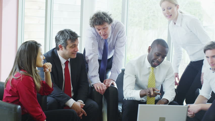 Multi ethnic team of professionals stand and shake hands at the conclusion of a business meeting. | Shutterstock HD Video #4403036