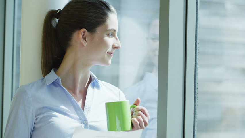 Businesswoman on her own takes a coffee break and looks thoughtfully out of the window | Shutterstock HD Video #4403612