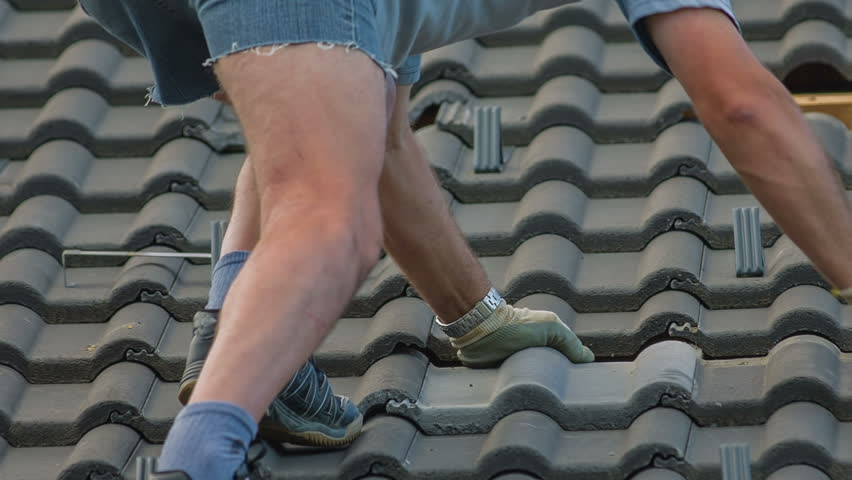 Fixing Roof Tiles After Hail Storm Close Up. Destroyed roof tiles on completely new house with no facade and no insurance yet. Man changes broken tiles because of hail storm destroyed the roof.