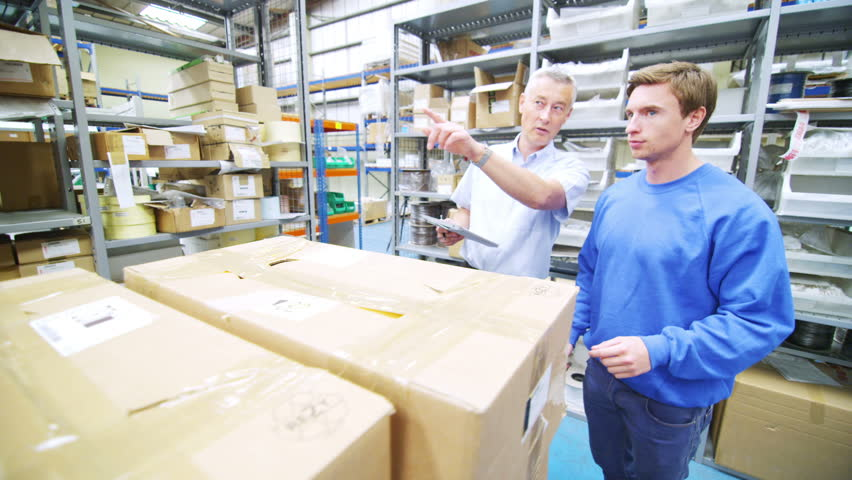 Team of male workers in warehouse or factory preparing boxes of goods for delivery.