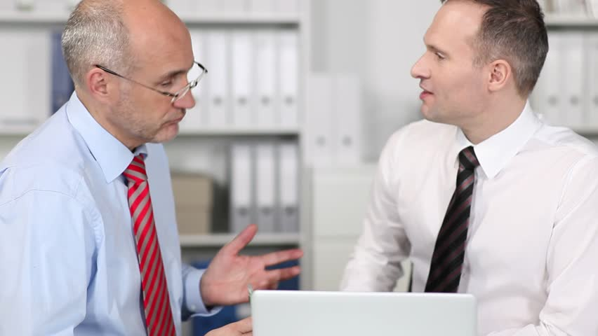 Two businessman gesturing at a the information on the screen of a laptop computer as they sit together having a meeting and discussion | Shutterstock HD Video #4423397
