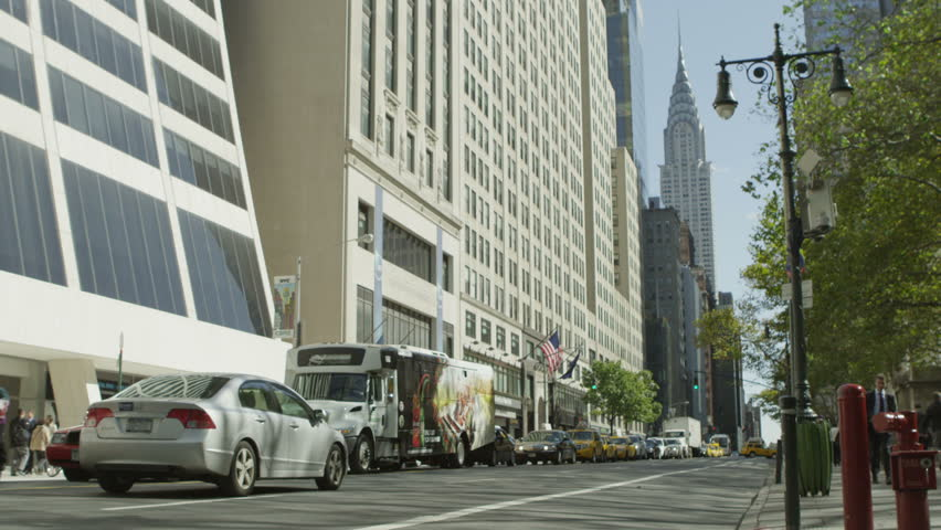 View of a quiet Manhattan avenue with cars and a few people on a clear bright day. The famous Chrysler building can be seen in the distance, In slow motion. | Shutterstock HD Video #4437437
