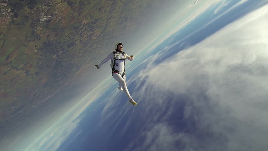 Skydiver woman freestyle in white clothes at sunny day