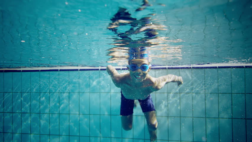 Happy cute little boy underwater is waving and smiling at the camera. #4459334