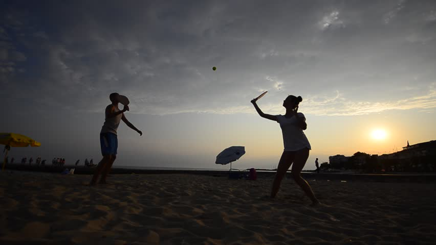 Beach leisure tennis game. Couple, Romantic  Beautifull teen and handsome gay are having fun at the beach sunset playing tennis ball and having fun.