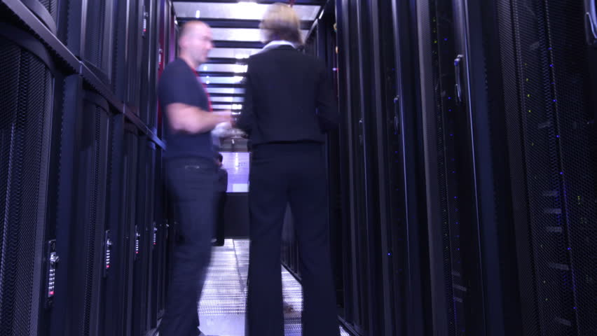 People working in computer server room data center. Walking along rows of super computers, racks and airconditioned cpu's. time lapse.