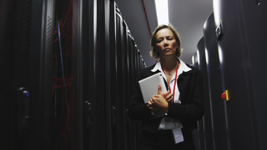 IT businesswoman inspects data center servers. Working in computer server room data center. Walking along rows of super computers, racks of airconditioned cpu's.