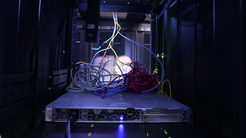 People working in computer server room data center. Walking along rows of super computers, racks and airconditioned cpu's. Technician rigging network cable.